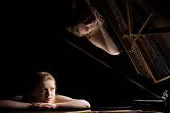 Girl after a grand piano Royalty Free Stock Photos