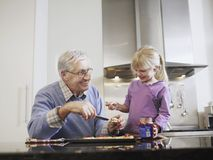 Girl And Grandfather Eating Breakfast Royalty Free Stock Photography