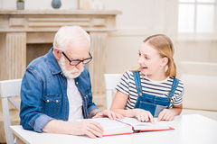 Girl and grandfather in eyeglasses reading book together at home Royalty Free Stock Images
