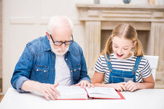 Girl and grandfather in eyeglasses reading book together at home Stock Photos