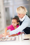Girl grandmother baking cookies Stock Images