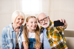 Girl with grandmother and grandfather sitting on sofa and taking selfie. Happy girl with grandmother and grandfather sitting on sofa and taking selfie Royalty Free Stock Image