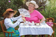 Girl and grandmother have a tea party. A charming spring garden is a perfect setting for a loving grandmother and her 6 year old granddaughter to have a tea Royalty Free Stock Images