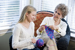 Girl with grandmother knitting in loving room. Grandmother teaching granddaughter how to knit Stock Photo