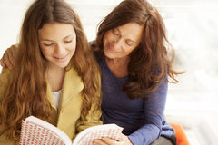 Girl and grandmother reading. Girl and grandmother studying together Stock Photos