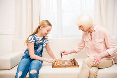 Girl with grandmother sitting on sofa and playing chess. Happy girl with grandmother sitting on sofa and playing chess Royalty Free Stock Photos