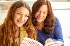 Girl and grandmother studying stock image