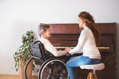 A girl with grandmother in wheelchair by the piano. A teenage girl with grandmother in wheelchair sitting by the piano at home, holding hands. Family and Stock Photos