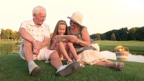 Girl with grandparents holding pc tablet. stock video footage