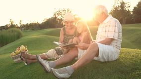 Girl with grandparents outdoors, photo album. stock video footage
