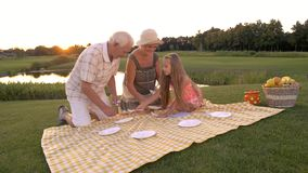 Girl and grandparents on picnic. Old man and woman with grandchild outdoors. Healthy meal on nature, picnic stock video