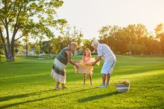Girl with grandparents, picnic. stock photo