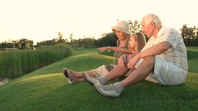 Girl and grandparents sitting outdoors. stock video footage