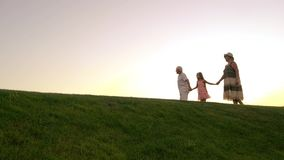 Girl and grandparents, sunset sky. stock video footage