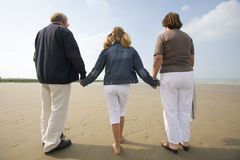 Girl and grandparents walking at the beach Stock Photos