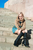 Girl of a granite ladder sitting on steps Royalty Free Stock Photos