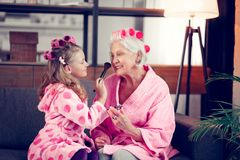 Girl and granny wearing hair rollers doing makeup together royalty free stock photo