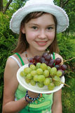 Girl and grape. Young girl wit green and black grape close up Royalty Free Stock Image