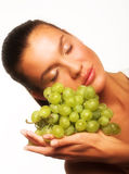 Girl with grape. Studio portrait of a girl with a bunch of grapes isolated on white background Royalty Free Stock Image