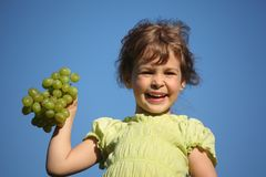 Girl with grape against blue sky Stock Photography