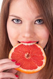 Girl and grapefruit in her teeth. The beautiful girl with red lips and grapefruit isolated on white Royalty Free Stock Image