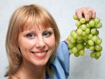 The girl and grapes. Girl holding in her hand a vine Royalty Free Stock Photography