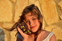 Girl with grapes. Israeli blond Girl at sunset with cluster of grapes on stones Royalty Free Stock Photo