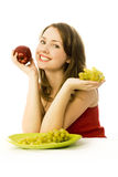 Girl with grapes and an apple Stock Image