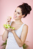 Girl With Grapes. Happy girl with green grapes over pink background indoors Stock Photography