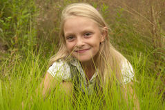 Girl in the grass. A small girl in the green grass royalty free stock image