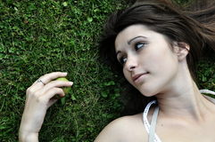 Girl in grass. Beautiful girl lying in grass with pear Stock Photo