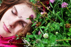 Girl in grass. Girl sleeping in grass with closed eyes Stock Image