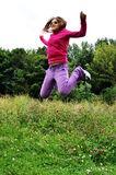 Girl in grass. Happy girl jumping in grass Royalty Free Stock Photos