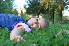 Girl in the grass. Little girl lying in the green grass Royalty Free Stock Photography