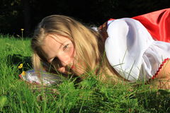 Girl on grass. Girl lying on the grass and playing with blades of grass Royalty Free Stock Photography