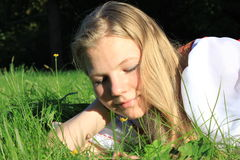 Girl on grass. Girl lying on the grass and playing with blades of grass Stock Images