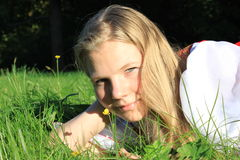 Girl on grass. Girl lying on the grass and playing with blades of grass Stock Photo