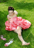 Girl on a grass. Happy fiancee in the rose dress of,sidyaschaya on a grass Royalty Free Stock Image