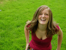 Girl in Grass. Young girl laughing sitting in grass stock photography