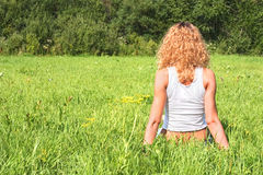 Girl on grass. Girl sits back on green grass Stock Photography