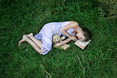 Girl on the grass with book. Girl is lying on the grass with book and  teddy  bear Royalty Free Stock Images
