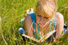 Girl in grass with book Royalty Free Stock Photo