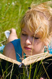 Girl in grass with book Royalty Free Stock Photos