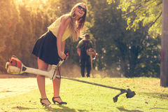 Girl with grass cutter in park. Royalty Free Stock Images
