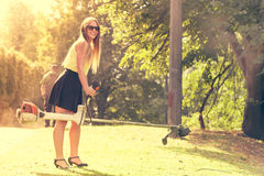 Girl with grass cutter in park. Stock Photos