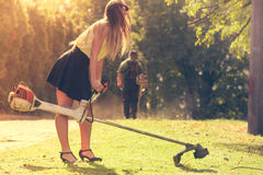 Girl with grass cutter in park. Royalty Free Stock Photo