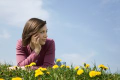 Girl in grass with flowers Stock Image