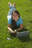 Girl in grass happily reading Royalty Free Stock Photo