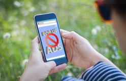 Girl in grass holding her smartphone with ads blocker. Girl in the grass holding her smartphone showing ads blocker. All screen graphics are made up royalty free stock images