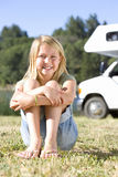 Girl (9-11) on grass with knees to chest, motor home in background, smiling, portrait royalty free stock images